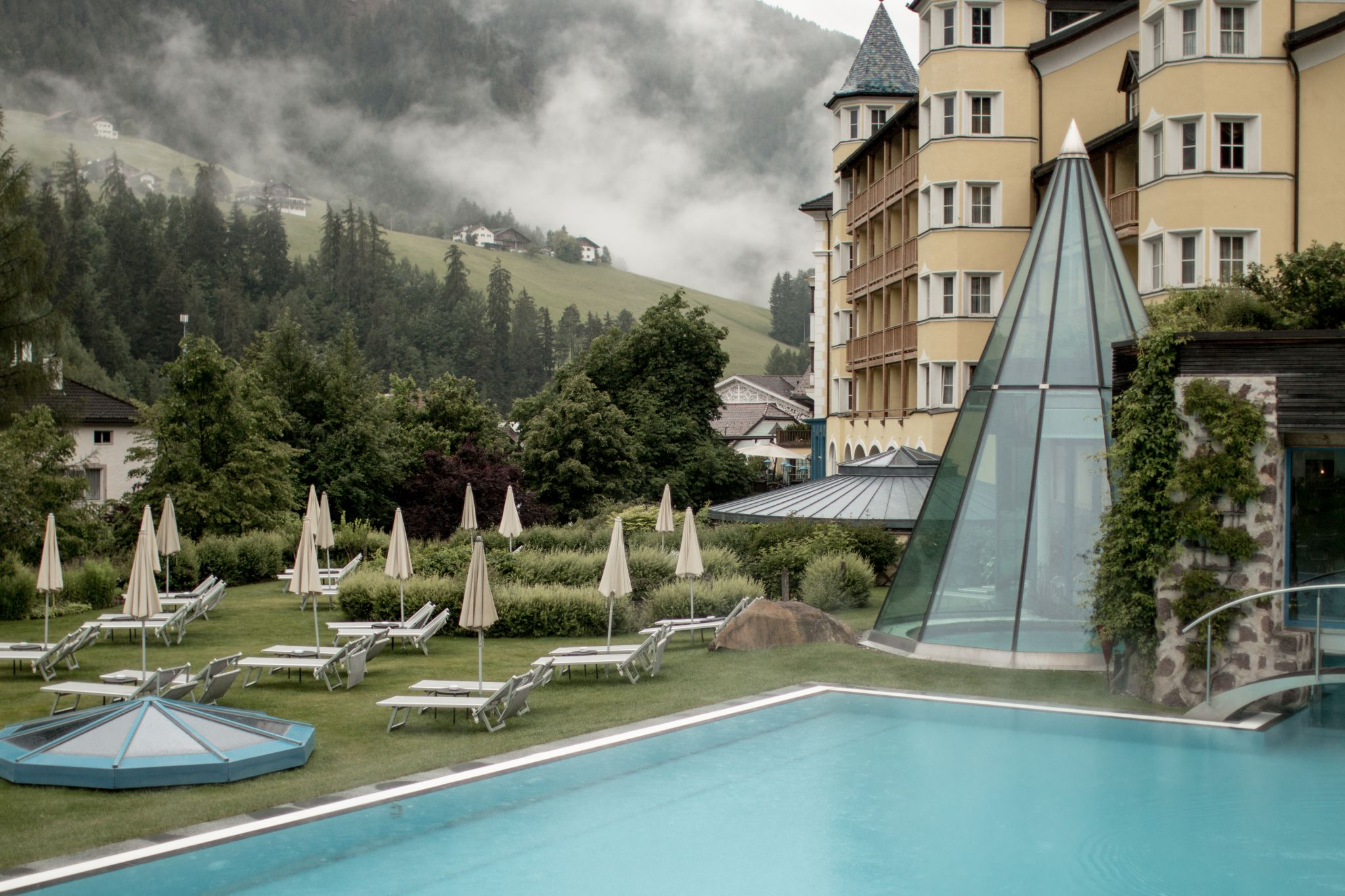 Adler Dolomites Hotel Ortisei Italy Hotel Hospitality Brand Photography Exterior poolside clouds glass pyramid